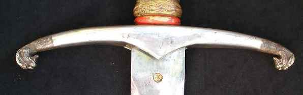 Гарда выполнена из позолоченного серебра, ее кончики выполнены в виде стилизованных голов леопардов.