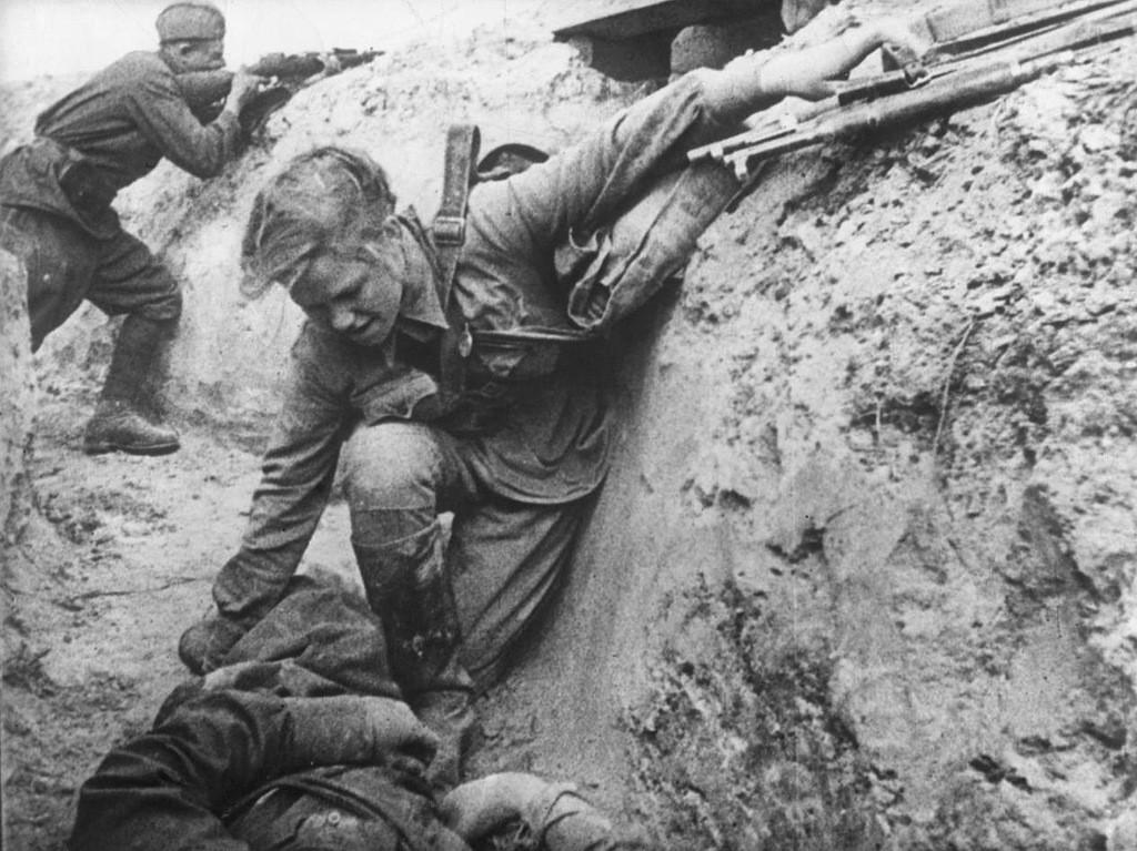 Советская санитарка оказывает помощь раненому красноармейцу под вражеским огнем.