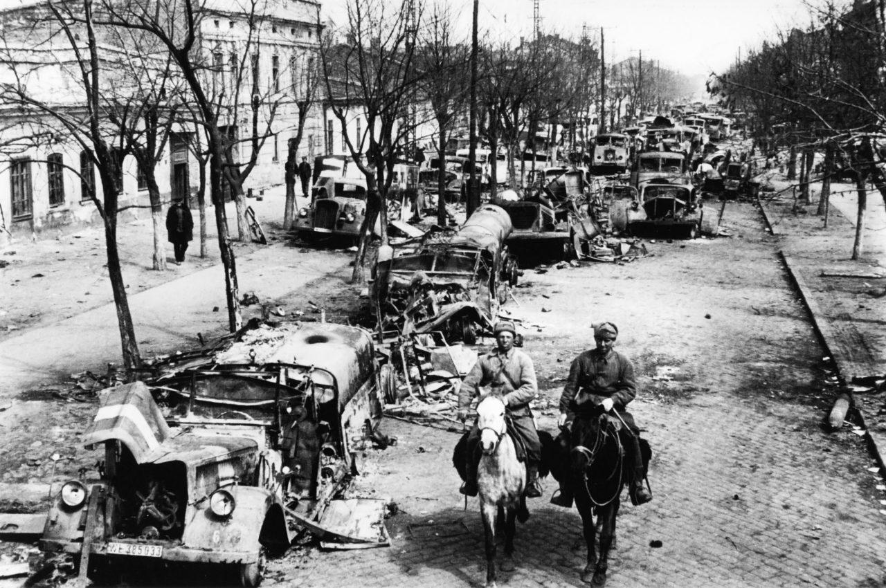 Советские солдаты едут по улице освобожденной Одессы, забитой брошенной немцами техникой. Фото — Дмитрий Бальтерманц. Апрель 1944
