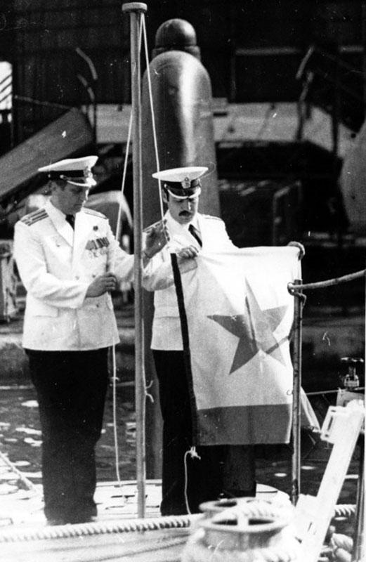 Командир Зеленский Ю.А. и инженер дивизиона живучести Ульянов А.В. поднимают военно-морской флаг.